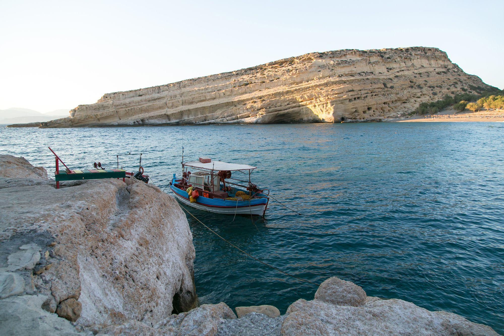 Boot in Matala auf Kreta, im Hintergrund Wohnhöhlen.
